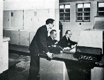 Computer pioneer Tom Kilburn (standing) and two colleagues at the Ferranti Mark I computer console
